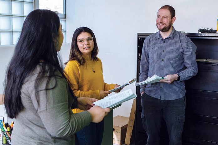 MONEY MATTERS: From left, Roxana Mercado and Ellie Parada, Capital Good Fund loan officers, and Andy Posner, founder and CEO, discuss strategies for helping clients navigate debt and personal finance at the company's office in Providence. / PBN PHOTO/RUPERT WHITELeY