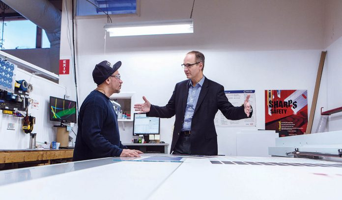 FOCUSED ON CUSTOMER SUCCESS: From left, Daniel Mercado, digital printing tech, and Renaud Megard, CEO, consult on a printing job in the design studio at Namplates For Industry Corp. in New Bedford. / PBN PHOTO/RUPERT WHITELEY
