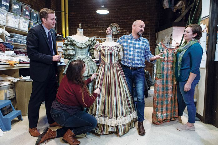 "A RICH, AND NOW PROSPEROUS HISTORY: From left, Tom Parrish, executive director; Meg Donnelly, cutter/draper; Curt Columbus, artistic director; and Amanda Downing Carney, costume shop director, review costumes for the upcoming production of ""A Christmas Carol.""   