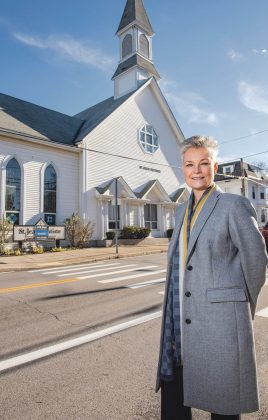 DESIRABLE LOCATION: BisMarc Properties broker and owner Brenda Marchwicki, listing agent for the Diocese of Providence sale of St. Jean Baptiste Church in Warren, stands outside the church, which is listed at $400,000. / PBN PHOTO/DAVE HANSEN