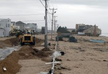 MAKING A PLAN: The R.I. Division of Statewide Planning is leading a project to support small businesses' ability to survive extreme weather events. Above, a machine clears sand off Atlantic Avenue in Westerly after the remnants of Hurricane Sandy battered Rhode Island's coast in 2012. / PBN FILE PHOTO/BRIAN MCDONALD