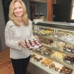 "SPECIALTY STORE: Christine M. Bourget is the owner of The Captain's Table in North Kingstown, specializing in gifts and specialty foods. Bourget is holding a tray of chocolates, with ""Wedding Cake"" at the rear and ""Birthday Party"" upfront.