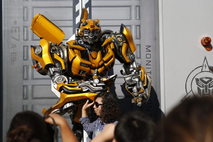 VISITORS POSE FOR PHOTOS with the Bumblebee character at the Universal Studios Hollywood theme park in California. / BLOOMBERG NEWS PHOTO/PATRICK T. FALLON