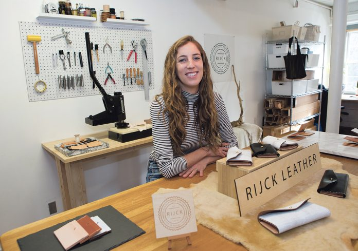 CREATIVE MIND: Alison Van Hemelrijck, owner of Rijck Leather, in her studio at Shady Lea Mill in North Kingstown. Van Hemelrijck previously worked in fashion design in California before switching gears to become a leather-goods manufacturer. / PBN PHOTO/KATE WHITNEY LUCEY