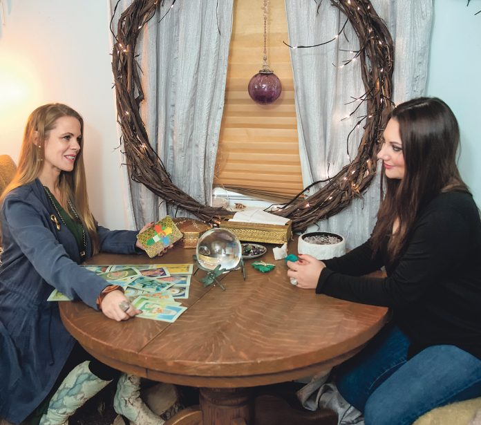 PSYCHIC READING: Roxanne Jasparro, left, owner of Bewitched of Scituate, a psychic reading and merchandise shop, does a reading for Trisha Wagner of Scituate.