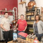 GROWING DISTILLERY: White Dog Distilling, incorporated as CAVE LLC, was founded in 2016 by Carlo Catucci, center, and his wife, Alecia, right, who partnered with longtime friends Eric Sylvestre, left, and Vin Greene, not pictured. Their micro-distillery and tasting room opened last April in a historic mill space in Pawtucket and will be moving to a larger retail location within the mill.