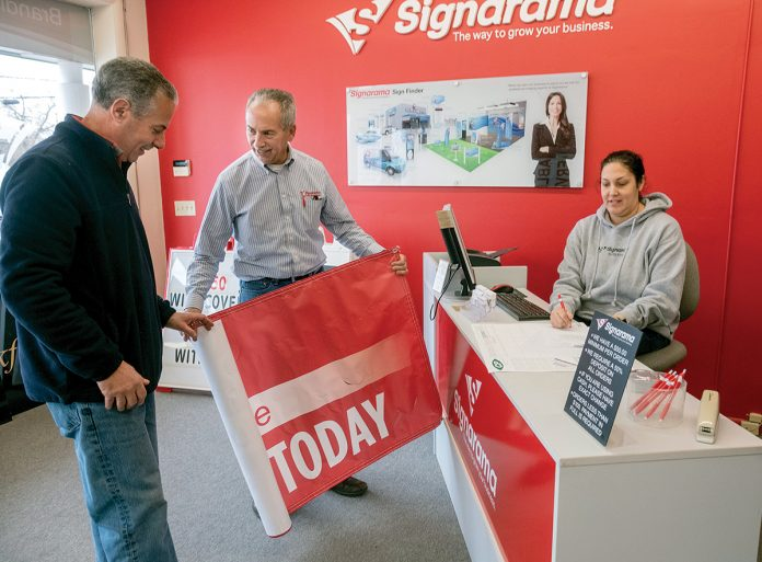 REWARDING WORK: Joe Lomastro, center, franchise owner of Signarama on Post Road in North Kingstown, with Tom Iacobucci, owner of Sears Hometown Store, and Lauren DeAquair, graphic designer.