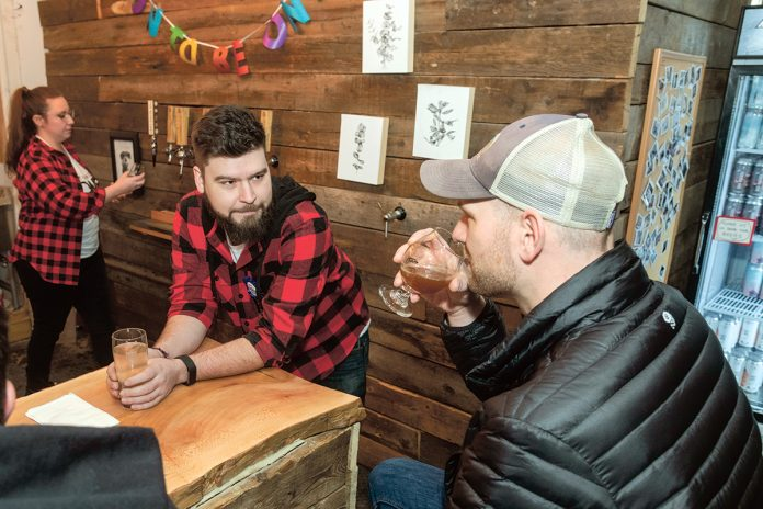"""PASSIONATE BREWER: Morgan Snyder Jr., center, is co-owner of Buttonwoods Craft Brewing. Snyder has worked in the brewing industry, including home brewing, since graduating college in 2011. Adam Henderson of East Providence tastes the """"30 Is The New 40"""" double IPA. At left is bartender Jennie Paquin. / PBN PHOTO/MICHAEL SALERNO"""