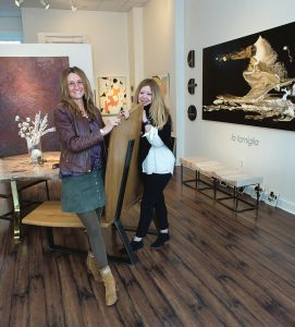 """LA FAMIGLIA: Bobbie Lemmons, right, founder and creative director of Atelier Newport, with Michele Maker Palmieri in the gallery with the recent show """"la famiglia,"""" which ran from Dec. 9, 2018, to Jan. 20. Art in the background includes Custom Sustainable Furnishings by Jeff Soderbergh; Medium Pearl Maple Dining Table and BookMatch Bench designed by Mark Hutkler; and oil-on-canvas paintings by Richard Nocera. / PBN PHOTO/KATE WHITNEY LUCEY"""