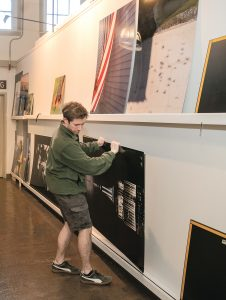 """PHOTO FINALIST: Preston Cottrell, computer numerical control operator and dye sublimation specialist at YJ Contemporary Fine Art in East Greenwich, adds Killian Moore's """"Between The Moon & New York City,"""" a 2018 Empire State Building photo contest finalist, to the rack for delivery. / PBN PHOTO/MICHAEL SALERNO"""