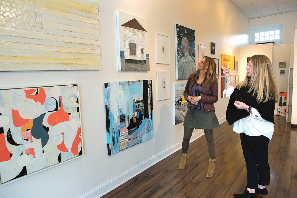 """GALLERY SHOW: Bobbie Lemmons, right, founder and creative director of Atelier Newport, and Michele Maker Palmieri admire artwork featured during the gallery's most recent show, """"la famiglia,"""" which ran from Dec. 9 through Jan. 20. / PBN PHOTO/KATE WHITNEY LUCEY"""