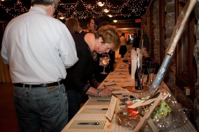 ATTENDEES MAKE THEIR bids on sports memorabilia during the Ocean State Waves' Black Tie & Blue Jeans fundraiser in 2016. This year's fundraiser will take place on Feb. 15 at The Towers in Narragansett. / COURTESY OCEAN STATE WAVES