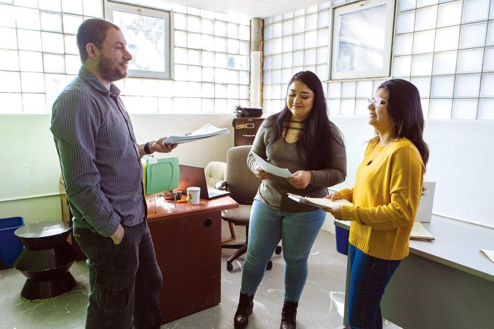 MONEY MATTERS: From left, Andy Posner, founder and CEO of the Capital Good Fund, and loan officers Roxana Mercado and Ellie Parada discuss strategies for helping clients navigate debt and personal finance at the company's office in Providence.  