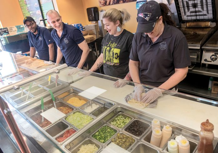 ENTREPRENEUR AT HEART: Matt Rusconi, second from left, franchise owner of Moe's Southwest Grill in East Providence, with, from left, Remon Gergis, director of operations; Alyssa Hawksley, shift lead; and Gail Brisson, general manager, as the team prepares food.                                                                                     /   PBN PHOTO/MICHAEL SALERNO