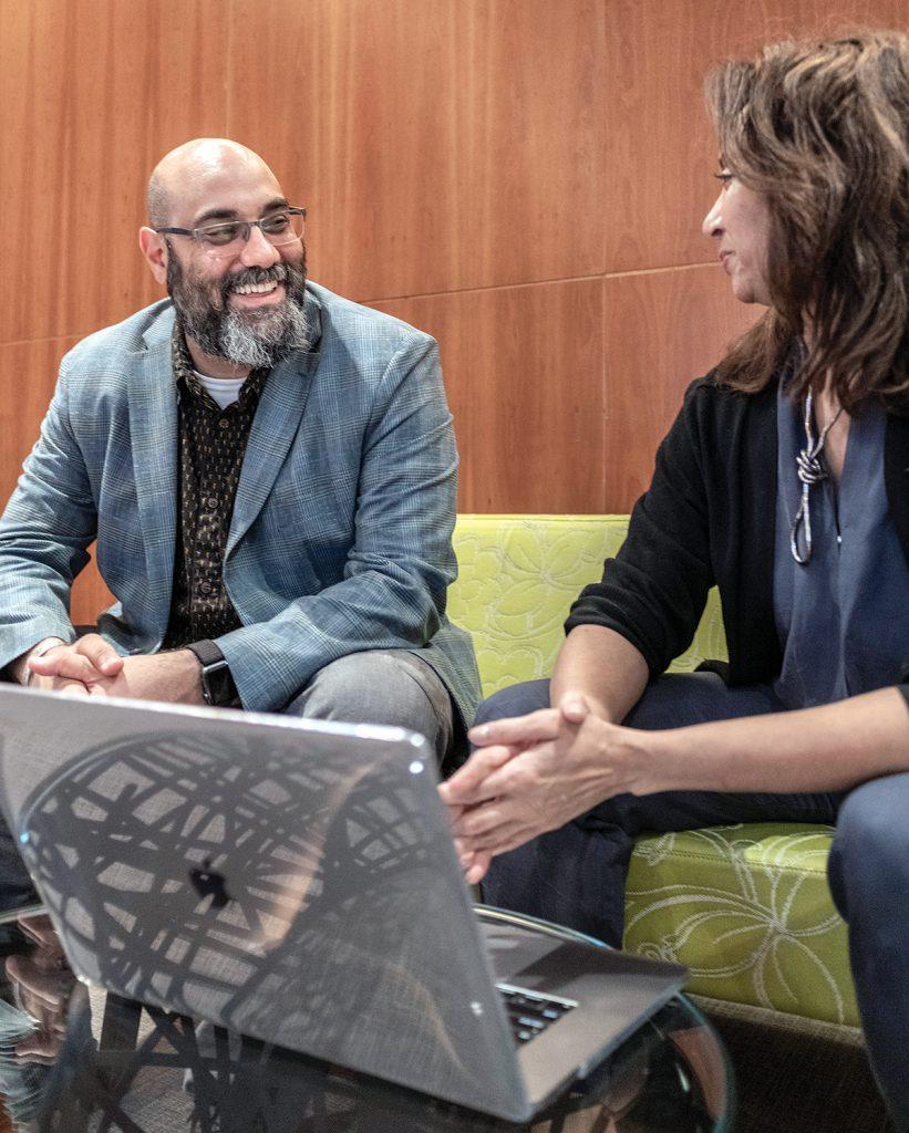 DEEPLY FOCUSED: Matthew Shenoda, social equity and inclusion vice president at Rhode Island School of Design, speaks with social equity inclusion fellow Rene Payne. / PBN PHOTO/MICHAEL SALERNO