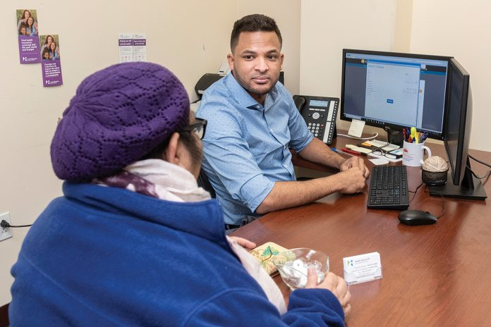 HELPING HAND: Customer-service representative Ramon Chevas German, right, assists a client with health insurance at a HealthSource RI center in East ­Providence.