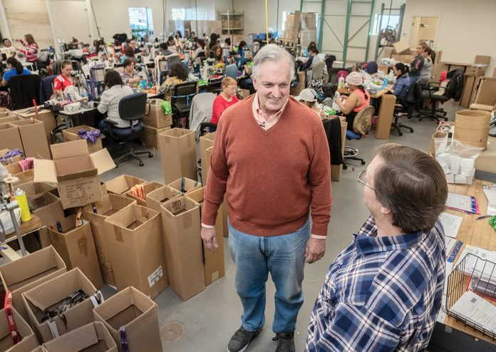 BETTER THAN EXPECTED: Adrien Hebert, left, co-owner and chief financial officer, speaks with Bob Laferriere, operations manager, at Trans-Tex, a company in Cranston that makes lanyards, sports merchandise, small-equipment pieces and other items. Hebert said business in January was better than expected.