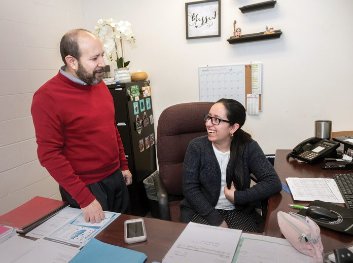 HIGHER PRIORITIES: Mario Bueno, executive director of Progreso Latino, a nonprofit that provides comprehensive social services to Latin Americans in Rhode Island, speaks with Johanna Tones, bookkeeper. Bueno said the 2020 census is not as high a priority for immigrants as other, more-pressing concerns, such as working and housing.