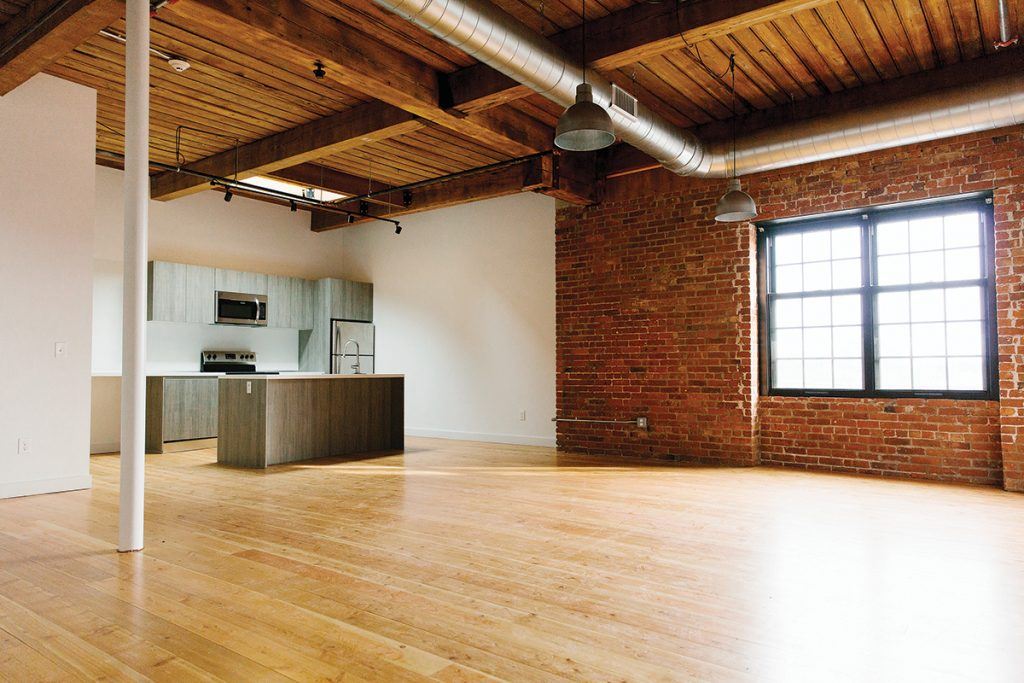 OPEN SPACE: An apartment at Pilgrim Lofts showcases both the open area for living space adjacent to the kitchen and a large window allowing in natural light. The space originally had boarded-up windows.