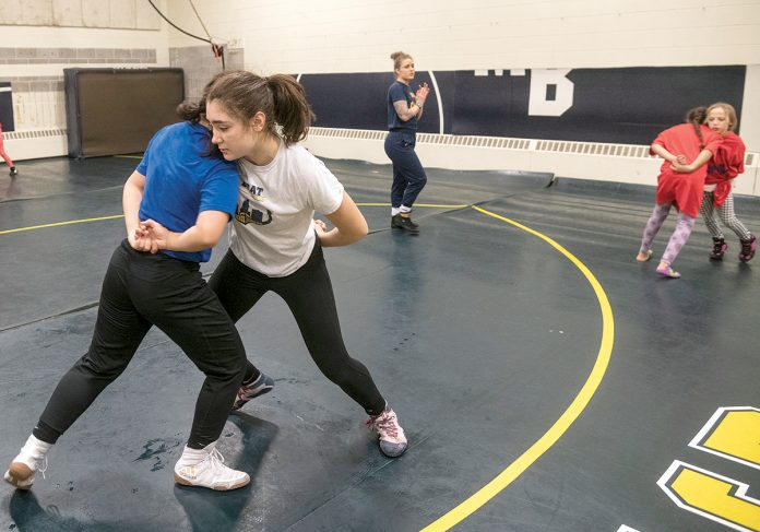 BEAT THE STREETS: Maricruz Flores, 12, left foreground, and Skylah Chakouian, 16, right foreground, spar as part of the Beat the Streets wrestling program at Moses Brown High School. In the background is Director Jacque Davis. At right are Alezia Greman, left, 10, and Ivy Latino, 7.