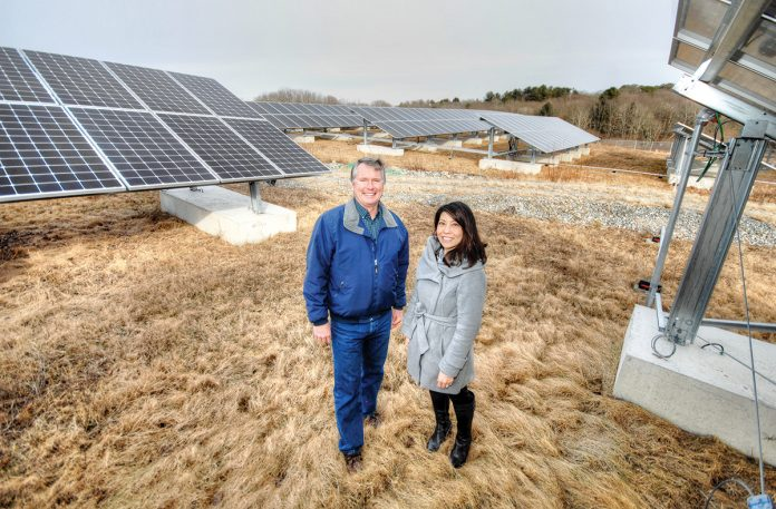 GREEN ENERGY: David Lamb, assistant director of utilities management at the University of Rhode Island, and Marcia Garcia, URI's sustainability officer, stand among a field of solar panels in South Kingstown. The solar array is part of the 40-megawatt South Kingstown Solar Collaboration facility, of which URI is one of three partners.  / PBN PHOTO/BRIAN MCDONALD