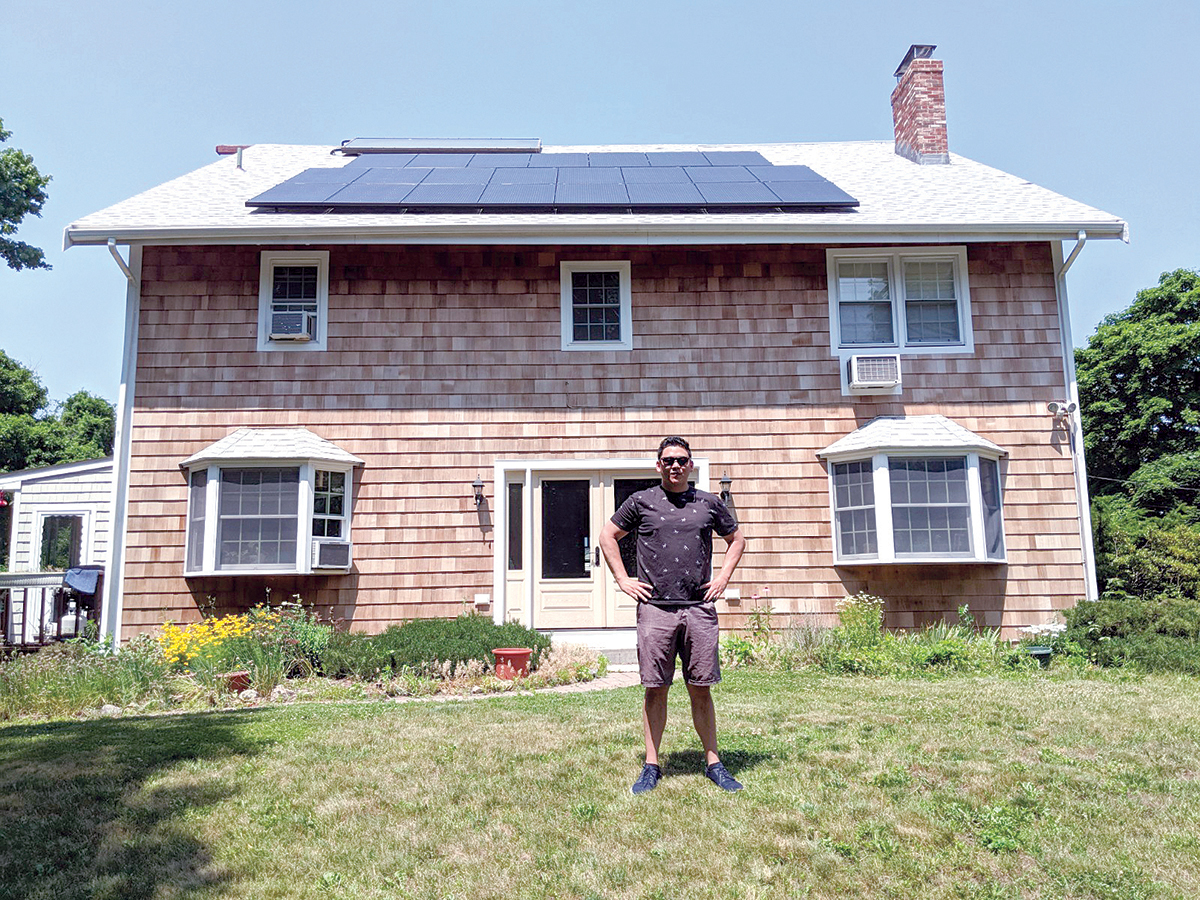 """NO-BRAINER: Ocean State Clean Energy CEO Kenny Hsieh said high energy prices, new solar technology and """"aggressive"""" incentives offered make the switch to solar power """"economically a no-brainer."""" He's standing in front of a Portsmouth home where his company installed solar panels last June. / COURTESY KENNY HSIEH"""