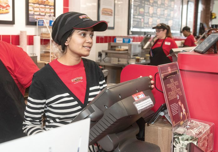 RAPID RESPONSE: Sejal Patel, foreground, co-owns the new Firehouse Subs franchise in Cranston. She's pictured with Alicia Martinelli, shift leader, and Sovannara Keo, crew member, in the background. The business collects donations for grants awarded to police and fire departments.