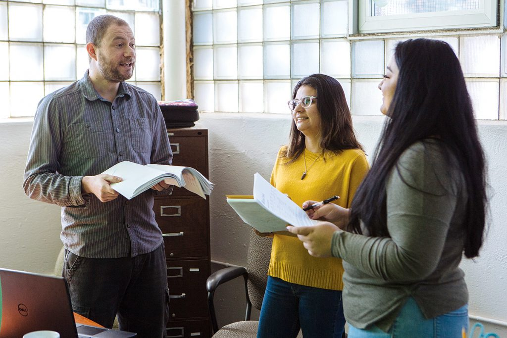 A BETTER WAY: Capital Good Fund founder and CEO Andy Posner, left, discusses strategies to help clients understand and deal with personal finance issues with loan officers Ellie Parada, center, and Roxana Mercado.  / PBN FILE PHOTO/RUPERT WHITELEY