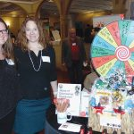AFTER HOURS: Dr. Day Care representatives Rebecca Compton, left, and Amy Vogel stand near their display, which includes a game wheel, during last year's Statewide Business After Hours networking event. This year's event will be held on March 26 at the Rhodes on the Pawtuxet in Cranston.  