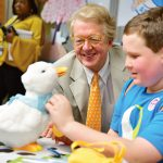 A NEW WAY TO COPE: Aflac Chairman and CEO Dan Amos and Ethan, a patient at the Aflac Cancer and Blood Disorders Center in Atlanta, examine My Special Aflac Duck, a product created by Sproutel Inc. to help children cope with cancer. The company has received a Rhode Island Innovation Voucher.  / COURTESY AFLAC