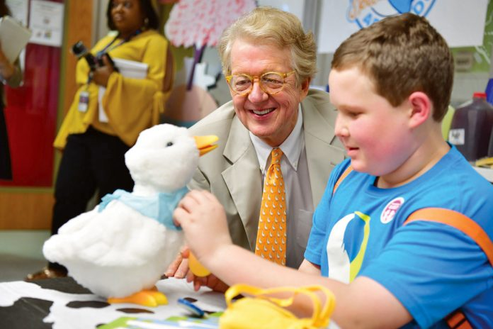 A NEW WAY TO COPE: Aflac Chairman and CEO Dan Amos and Ethan, a patient at the Aflac Cancer and Blood Disorders Center in Atlanta, examine My Special Aflac Duck, a product created by Sproutel Inc. to help children cope with cancer. The company has received a Rhode Island Innovation Voucher. 