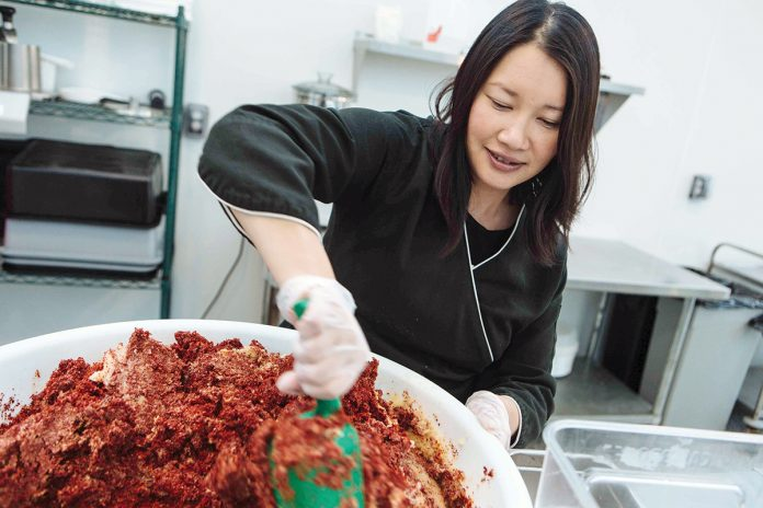 MIX IT UP: Chi Foods CEO Minnie Luong stirs the ingredients for a fresh batch of kimchi in the company's kitchen. / PBN PHOTO/RUPERT WHITELEY