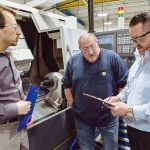 CHECKING IN: Plant Manager Craig Danko, left, and Production Manager Joe Cairo, right, review safety checklists with Michael Simpson, a setup machinist, at Saint-Gobain in Bristol. / PBN PHOTO/RUPERT WHITELEY