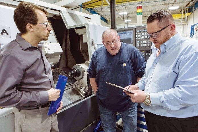 CHECKING IN: Plant Manager Craig Danko, left, and Production Manager Joe Cairo, right, review safety checklists with Michael Simpson, a setup machinist, at Saint-Gobain in Bristol.