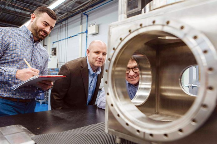 A KEEN EYE: President and CEO George Mock, right, inspects a piece of machinery at Nye Lubricants, along with Jason Galary, center, director of research and development, and Gus Flaherty, manager of engineering development and applications. / PBN PHOTO/RUPERTWHITELEY