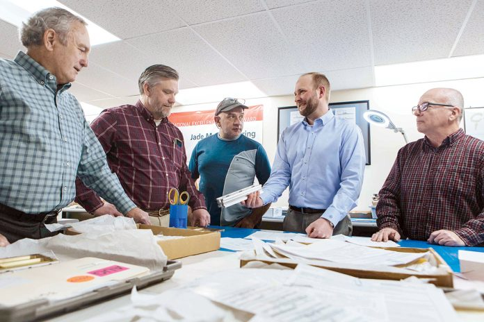 TABLE TALK: From left, Jade Manufacturing President Don Boyle discusses a component with Quality Manager Ron Olf, Assembly Manager Donald Campbell, Vice President Chris Burch and Director of Manufacturing Steve Gruner.   / PBN PHOTO/RUPERT WHITELEY