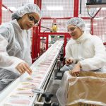 FOOD INSPECTORS: Employee Maria Velez, left, and CEO Navyn Salem check food packages as they move along the production line at the Edesia plant in North Kingstown.