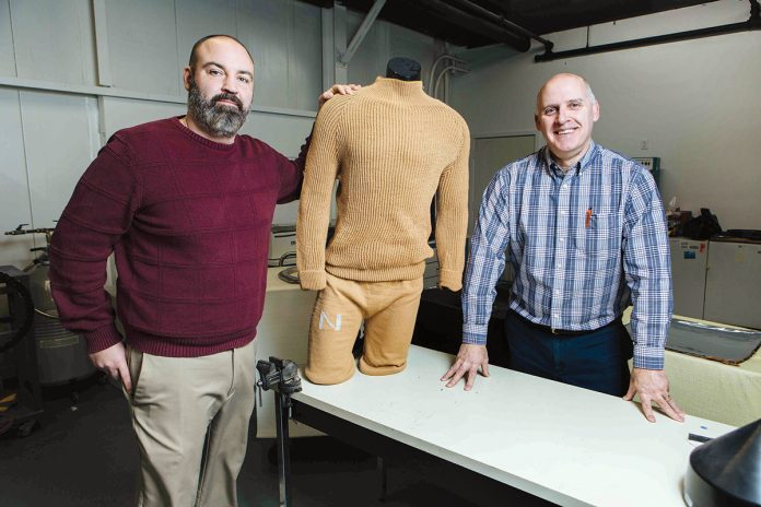 CUTTING-EDGE CLOTHES: Response Technologies President Ed Bard, left, and CEO David Pettey display a garment made using the company's 3D textile process, which required no cutting or sewing. Produced for the U.S. Navy, the garment could be made to be fire-resistant and embedded with smart features. / PBN PHOTO/RUPERT WHITELEY