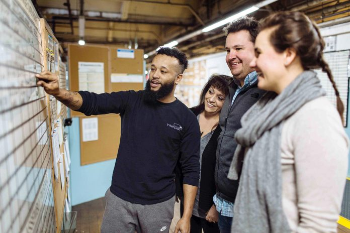 ALL ABOARD: Mechanic Jose Duarte, left, consults a board that's integral to International Packaging's lean protocols. With him, from left, are Lucy Amaral, production manager; James Kilmartin, purchasing manager; and Erin Kilmartin, marketing and creative director. / PBN PHOTO/RUPERT WHITELEY