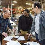 MINDING THE STORAGE: Steve Lorello, left, account manager, discusses logistics with warehouse associate Donald Roderick, center, and Gordon Fox, team leader, at Dean Warehouse Services.