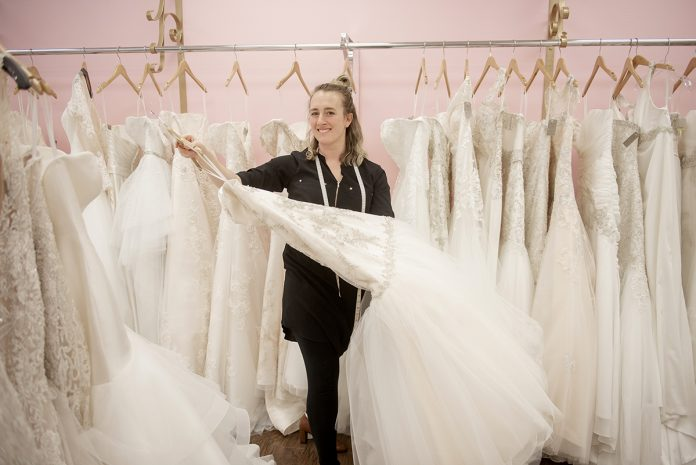 "NEW OWNER: Kayla Thompson is the owner of Melissa Ashley Brides in Westerly. Thompson bought her wedding dress at the bridal shop seven years ago and befriended the former owner, Denise Pellegrino, who later hired Thompson. The pair came to a ""personal finance agreement"" that transitioned ownership to Thompson when Pellegrino was ready to sell.