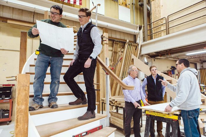 CUSTOM STAIRS: North Atlantic Corp. employee Dan Lovenbury, left, reviews plans for a custom-made staircase with Chief Operating Officer John Humphrey. CEO Peter Humphrey, third from right, talks about another project with Chief Digital Officer Michael Humphrey, second from right, and employee Joe Costa.