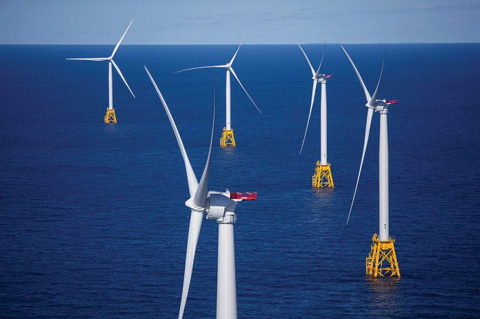 THE PUBLIC UTILITIES COMMISSION is set to open a public hearing Tuesday night on Orsted US Offshore Wind's proposed Revolution Wind project, as outlined in a contract filing by National Grid. Shown here are offshore wind turbine's near Block Wind developed by Deepwater Wind, which Orsted now owns. / BLOOMBERG NEWS/ERIC THAYER