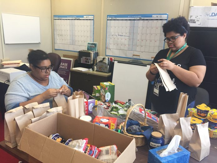COMMUNITY COLLEGE of Rhode Island students Leyshell Williams, left, and Sabrina Melki prepare bags of food and household products at the food pantry at CCRI's Lincoln campus ahead of the pantry's official opening on Monday. / COURTESY COMMUNITY COLLEGE OF RHODE ISLAND
