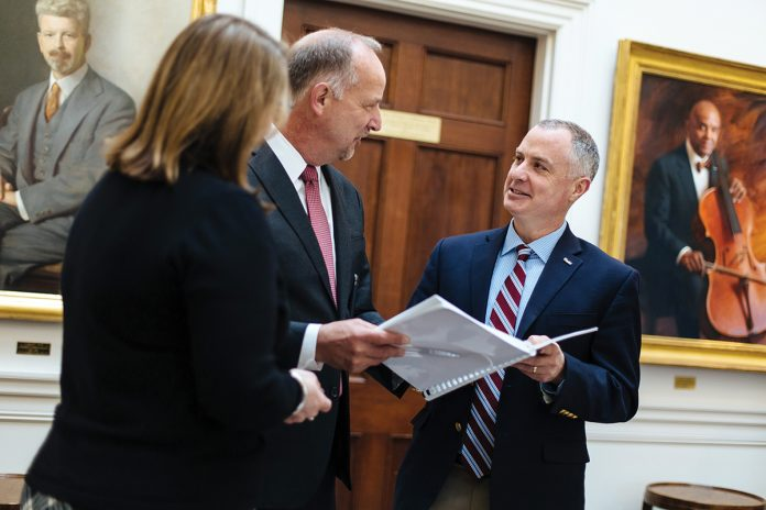 COLLEGIAL CONVERSATION: Brian Douglas, right, Wheaton College executive vice president of finance and administration, reviews a project report with President Dennis Hanno, center, and Associate Provost Meg Kirkpatrick.