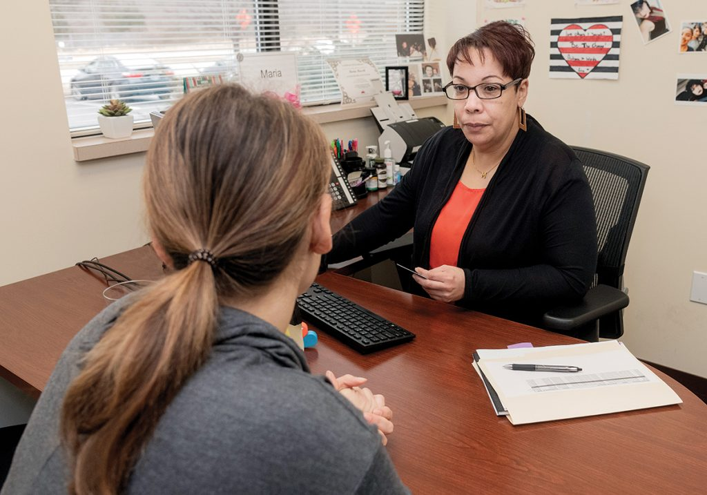 INSURANCE ASSISTANCE: HealthSource RI customer-service representative Maria Masseb, right, speaks with a client at an HSRI center in East Providence.  / PBN FILE PHOTO/MICHAEL SALERNO
