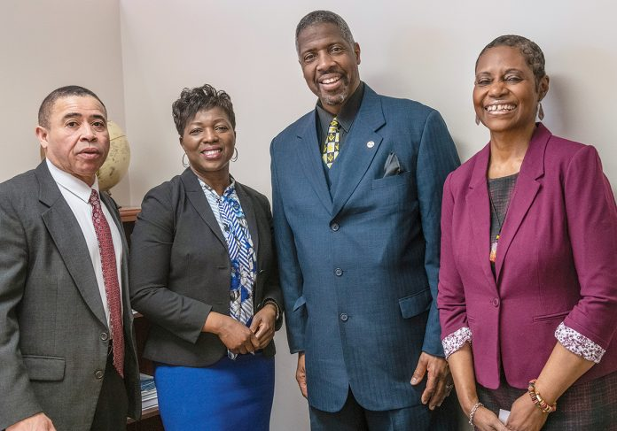 SHOWING UP: Rhode Island Black Business Association President Lisa Ranglin meets with members at the office. From left: Retired R.I. State Police Lt. John P. A'Vant; Ranglin; Clarence R. Sneed Jr., CEO of S&S Trucking; and Donna M. Sams, Community College of Rhode Island campus coordinator, Providence and Lincoln. / PBN PHOTO/MICHAEL SALERNO