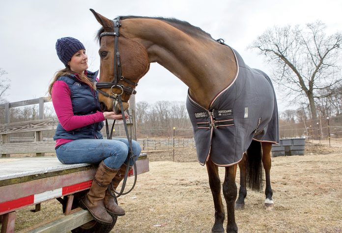 HORSE ENTHUSIAST: Kaitlyn Naughton, an equine insurance specialist at Naughton Insurance in East Providence, visits her horse, Baron, at Stony Creek Farm in Swansea. She said most equine insurance policyholders are middle-class people who are horse enthusiasts and recreational riders.