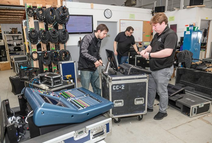 GEAR PREP: Advanced Production and Design in Warwick provides audio and visual equipment and other event-production services. From left, Evan Perry, chief operating officer; Patrick Boutwell, production and warehouse technician; and Adam Ramsey, CEO, prep gear for a job.