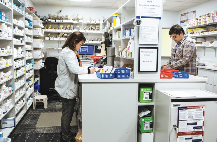 OPIOID STUDY: Susan Lim, site manager, and Joe Robillard, pharmacy technician, work on prescription orders at a Genoa Healthcare pharmacy inside a Gateway Healthcare clinic in Pawtucket. Genoa is collaborating with Rhode Island Hospital and CODAC Behavioral Healthcare on a study examining the effectiveness of pharmacist-delivered, medication-assisted treatment for opioid-use disorder.